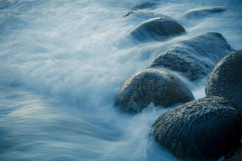 Close-up from waves swelling over rocks on the shore. Long exposure. royalty free stock photos