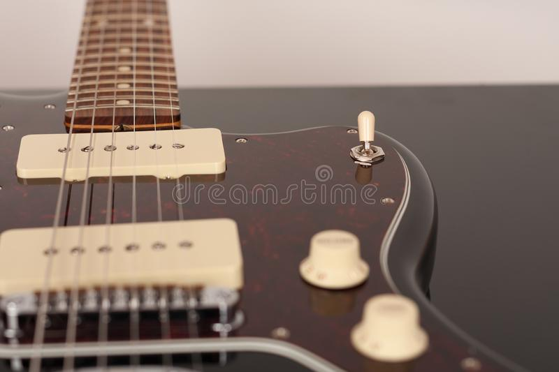 Close up of 3 way pickup switch on black electric guitar. Studio shoot. Red tortoise shell pickguard, alder body, two single coil royalty free stock photography