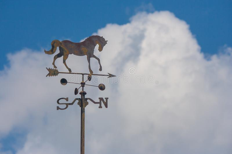 Close up weather vane or wind direction indicator on rooftop of house with blue sky in the background at countryside. stock photo