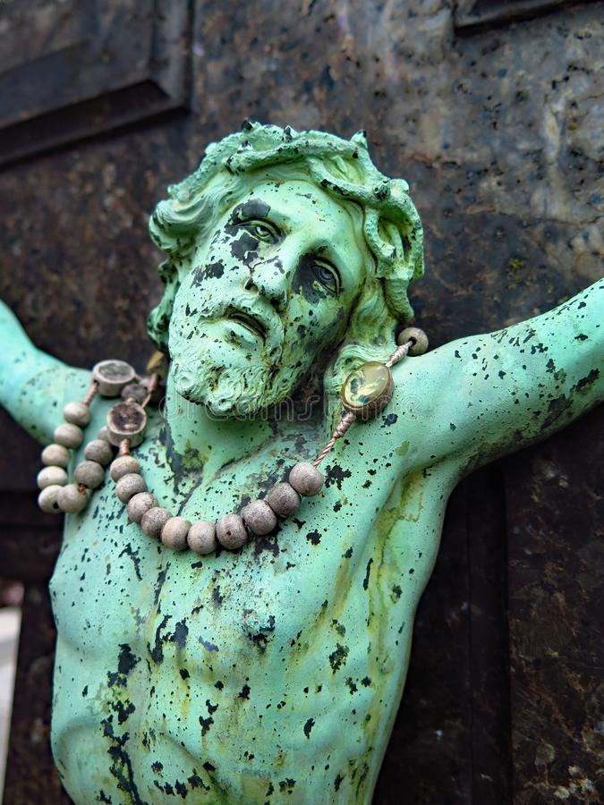 Weathered bronze crucifix on a marble tombstone stock photo