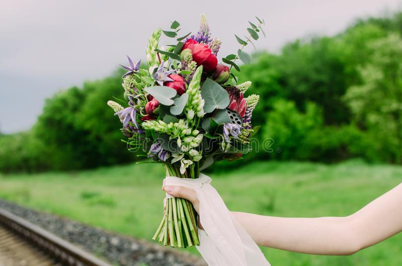 Close up of wedding bouquet with green, red and violet flowers and white ribbon. Bride with wedding bouquet in her hands. royalty free stock photography