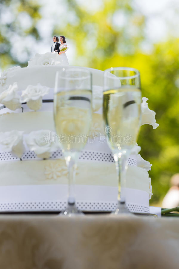 Close-up of wedding cake and champagne flutes. At the park stock photo