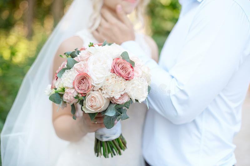 Close-up wedding couple standing side by side holding bouquets of flowers in white-pink colors stock photos