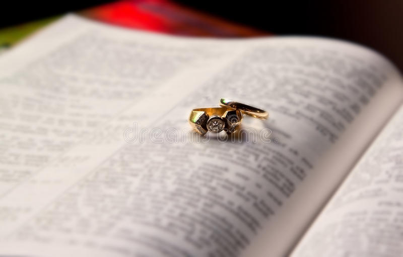 Close up of wedding rings. Lying on an open Bible stock photography