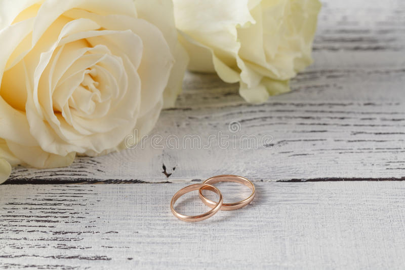 Close-up of wedding rings on background of roses royalty free stock images