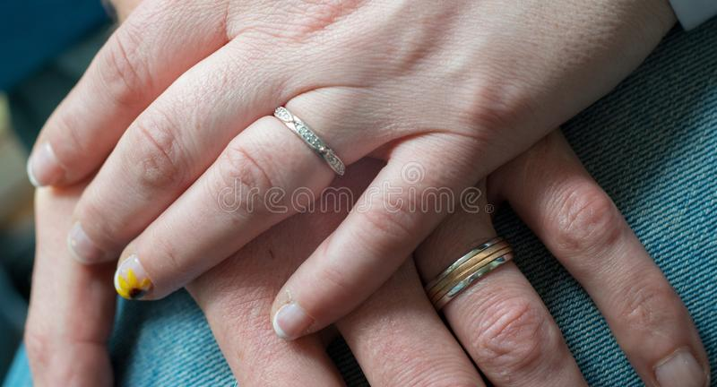 Close Up of Wedding Rings and a Flower with a Yellow/Orange Centre. Signifying love and couples royalty free stock photography