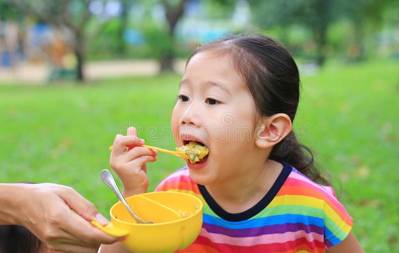Close-up weinig Aziatische tijd van het kindmeisje ongeveer 4 jaar oude het eten rijst door zelf in de tuin openlucht royalty-vrije stock foto's