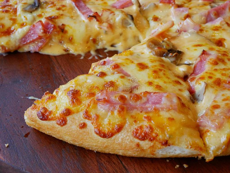 Well-done fresh appetizing mushroom, ham, cheese pizza being served on a wooden tray, ready to eat. Close up of well-done fresh appetizing mushroom, ham, cheese royalty free stock images