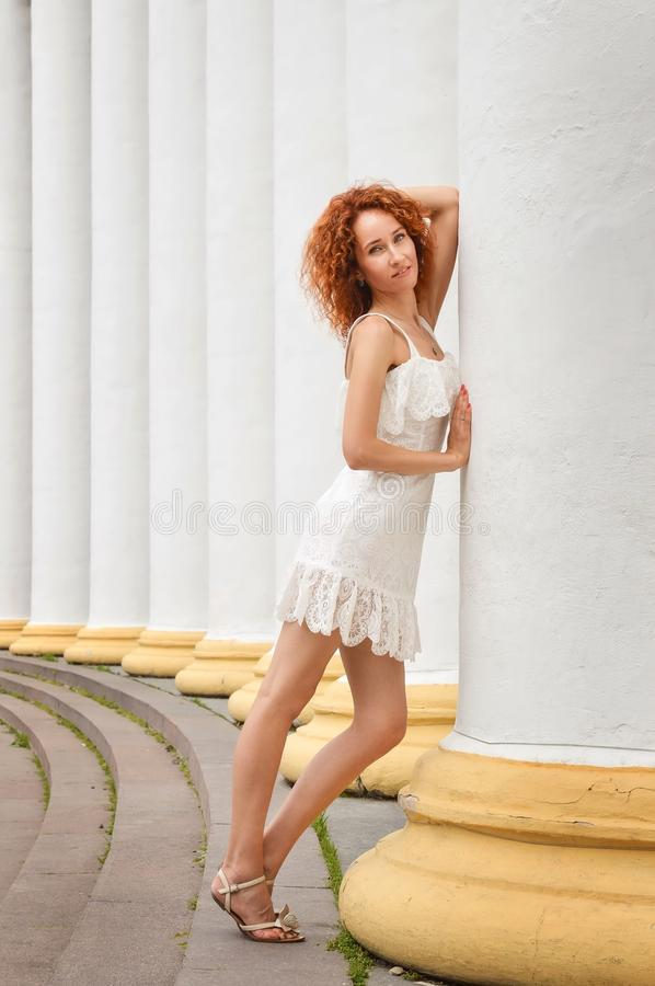 Close up. Well-groomed red-haired slim girl posing near white columns and looking at the camera. Copy space stock photography