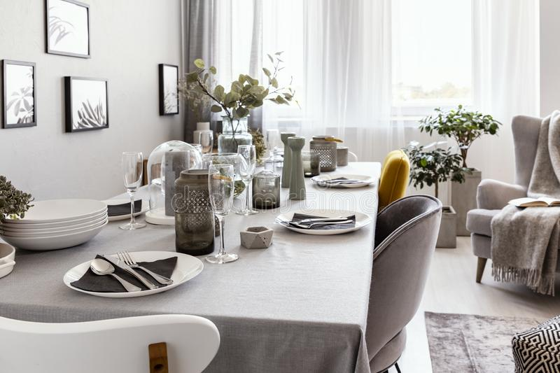 Well-laid table with plates and glasses in a grey dining room interior. Real photo stock images