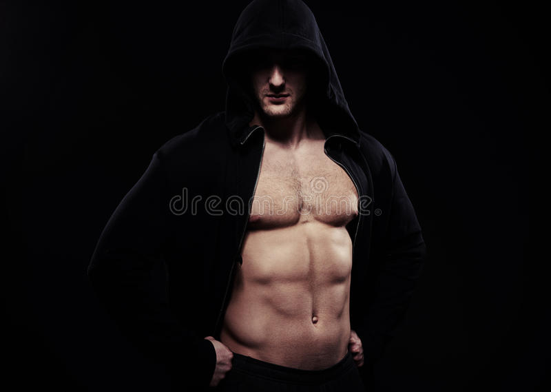 Close-up of well trained muscular body. Close-up of guy in dark sport jacket with hood over his head showing well trained muscular body, hands on hips royalty free stock photography