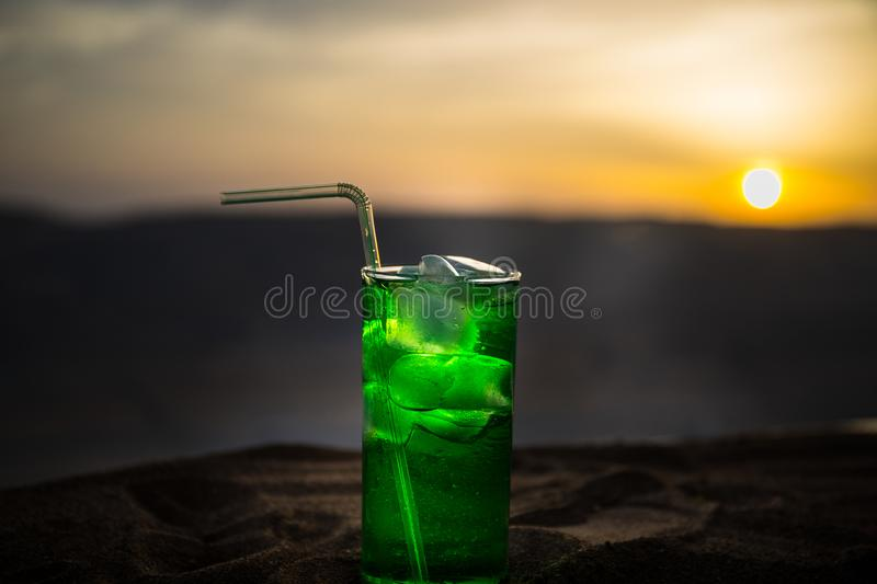 Close up wet glass of green cold mint drink, colorful orange sunset background on the terrace. Cooling summer drink. Summer fresh royalty free stock photos