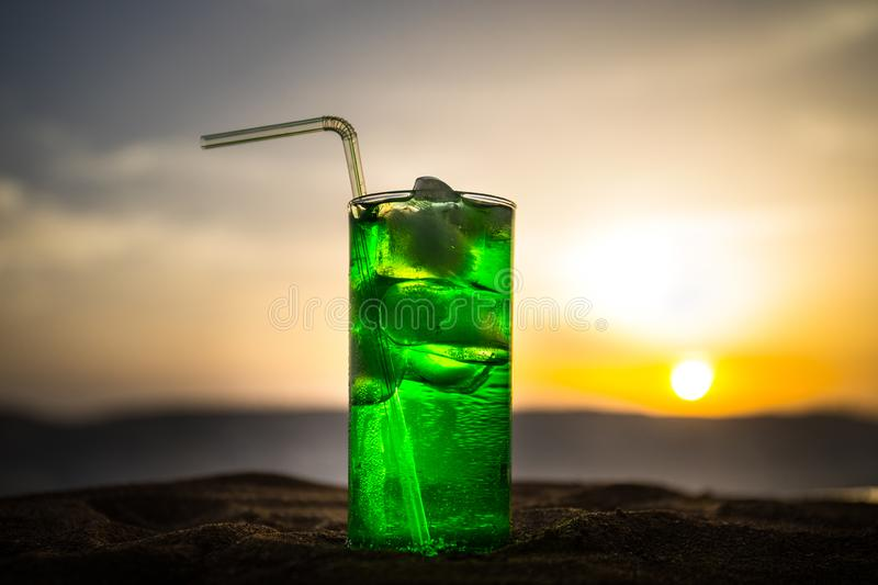 Close up wet glass of green cold mint drink, colorful orange sunset background on the terrace. Cooling summer drink. Summer fresh royalty free stock photography