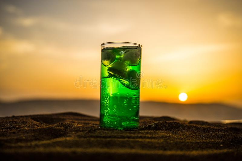 Close up wet glass of green cold mint drink, colorful orange sunset background on the terrace. Cooling summer drink. Summer fresh stock images