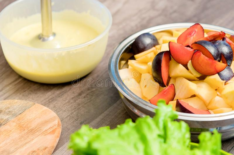 Close-up of whipping a mixture of homemade mayonnaise with a blender in a plastic bowl. Sliced apples and plums in a stock photography