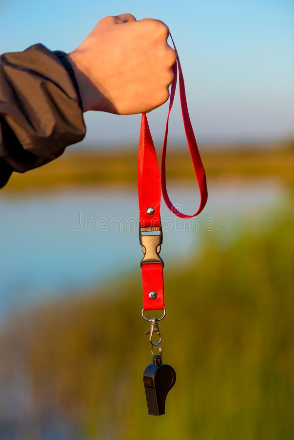 Close-up of a whistle on a lace in a male hand royalty free stock photo