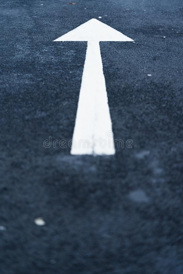 White Arrow on Tarmac Road. A close up of a white arrow pointing upwards on a tarmac road royalty free stock images