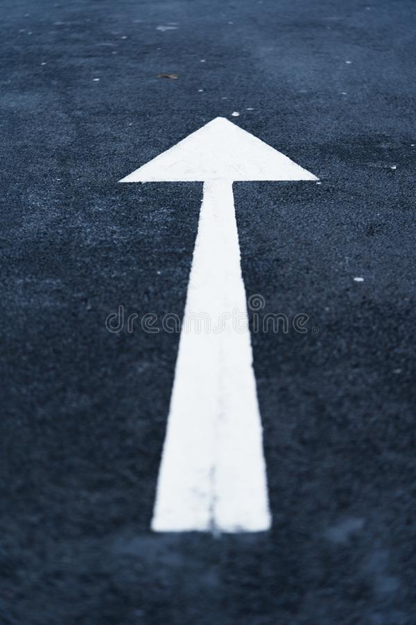 White Arrow on Tarmac Road. A close up of a white arrow pointing upwards on a tarmac road stock photography