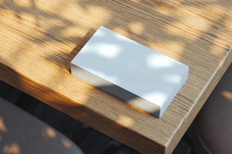 Close up of white blank illuminated by daylight business cards set on wooden table, 3d rendering. royalty free illustration