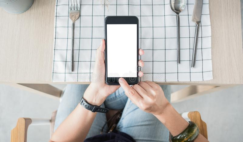 Close up white blank screen mobile over restaurant table order food online royalty free stock photo