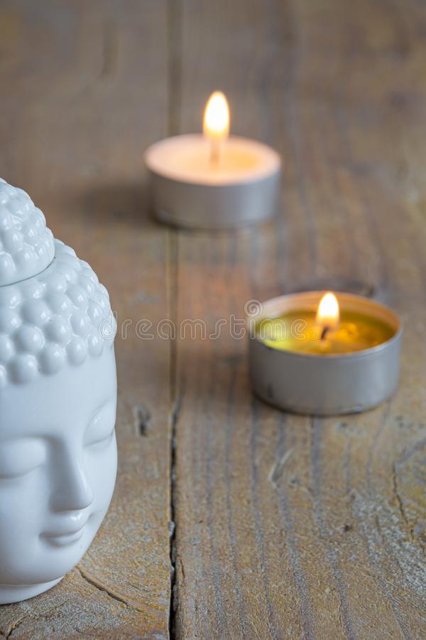 Close-up of white buddha figure and candles on worn wooden royalty free stock images