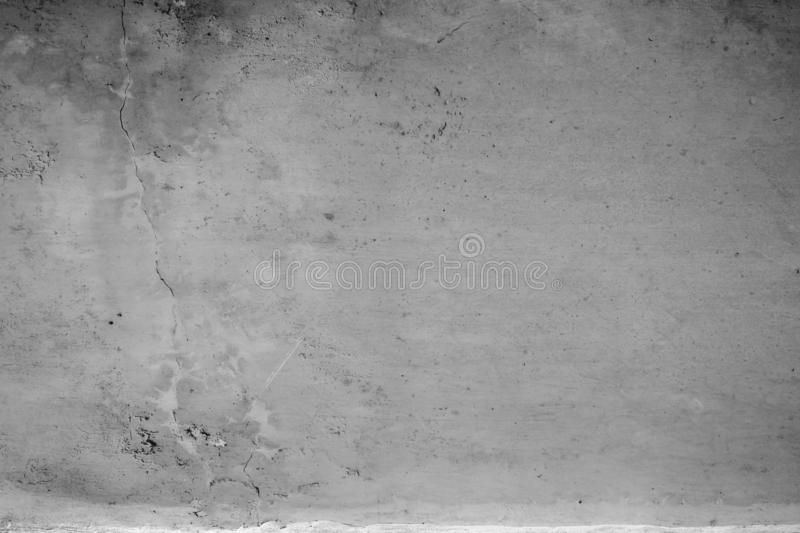 Close-up of White cement crack wall and peeled paint caused by water and sunlight. Peel wall of White house paint with black stain. Black and White of Texture stock photo