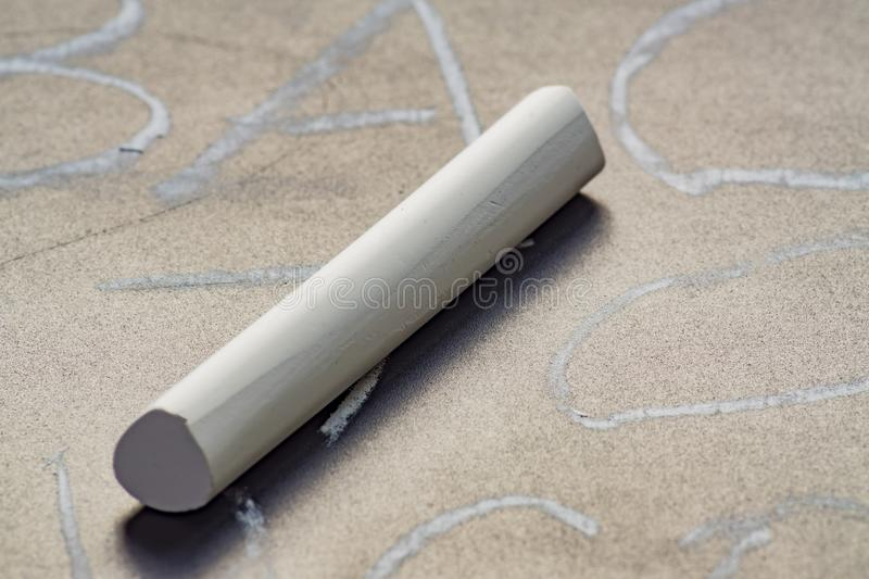 Close up of white chalk on blackboard with written words stock image