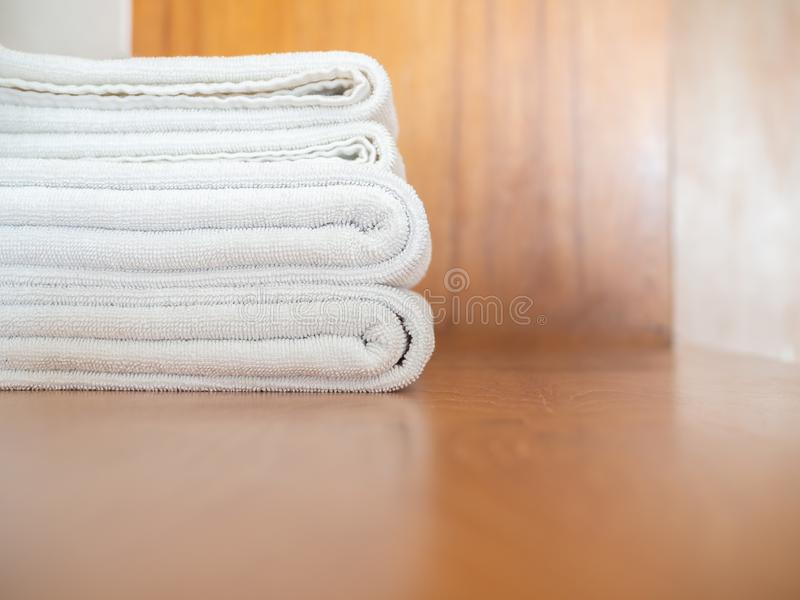 White clean towels on wooden surface and white wall background. Close-up white clean towels on wooden background with copy space stock image