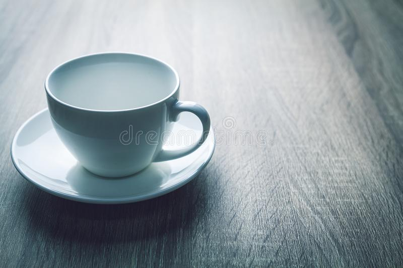 Close up white coffee cup on black wood table near window stock photography