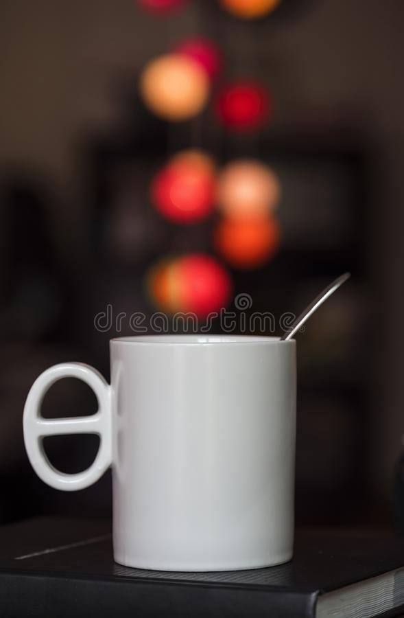 Close up white coffee cup on the book and colorful blur light bo stock photos