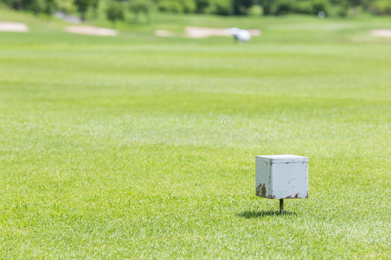 Close-up white color wooden tee off area or tee box with blurred. Natural green golf course in background stock photo