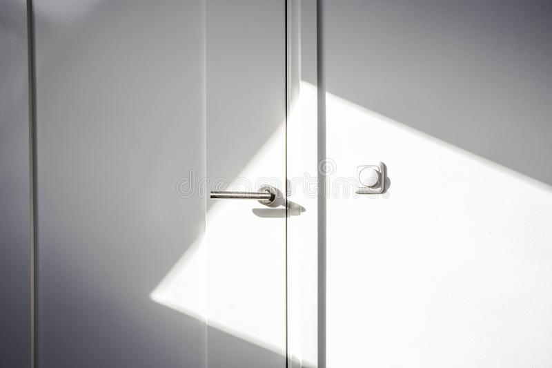Close-up white door with sunlight. Chrome door ,The light switch on the wall modern design empty and clean stock image