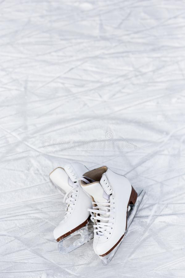 Close up of figure skates over ice background with marks from skating or hockey royalty free stock photos