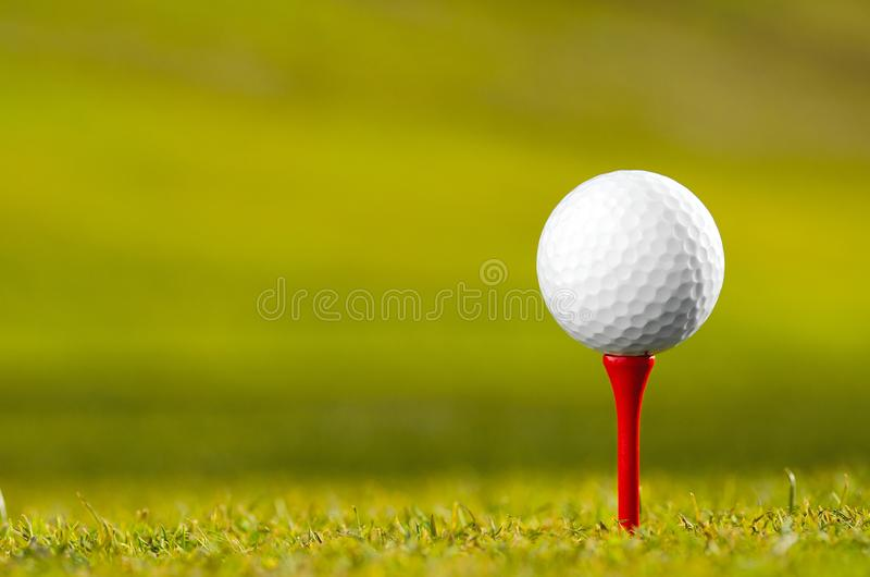 Golf ball on tee. Close up of white golf ball on red tee on grass royalty free stock image