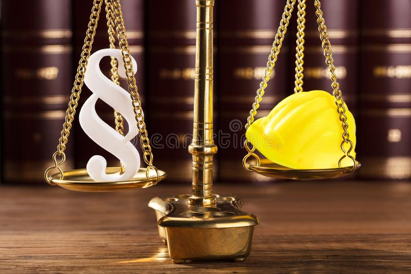 Paragraph Symbol And Hard Hat On Justice Scale. Close-up Of White Paragraph Symbol And Yellow Hard Hat On Justice Scale royalty free stock photography