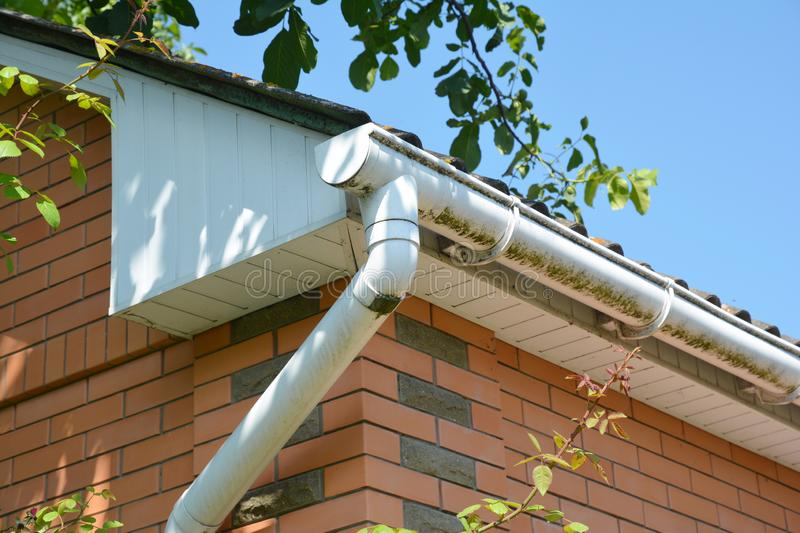 White plastic rain gutter. House roof guttering repair. stock images