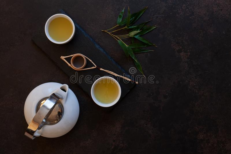 Close up of White porcelain Asian tea set with green Japan Matcha tea on black stone desk stock image