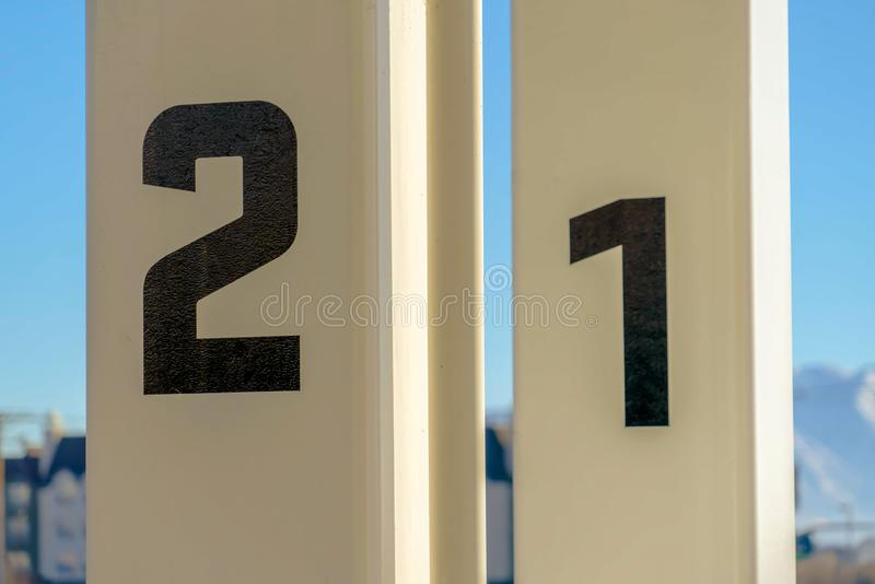Close up of white rectangular posts with numbers painted on the surface. Building and sky cna be seen in the blurry backgroun on this sunny day stock images