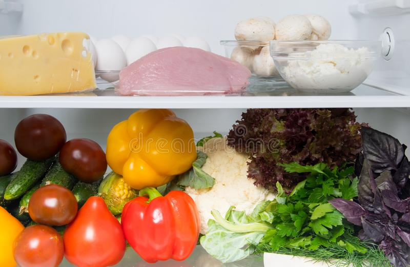 Close-up, in the White Refrigerator food stock, on the top shelf are eggs, fish, mushrooms, cottage cheese, turkey meat, cheese, royalty free stock image