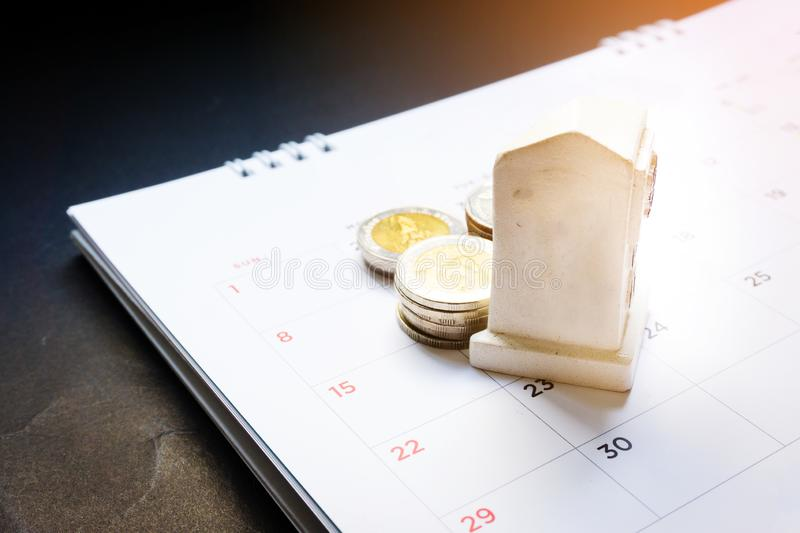 Close up white road kilometer pole toy and money baht coin on the monthly planner calendar on black background. Summer calendar sc royalty free stock image