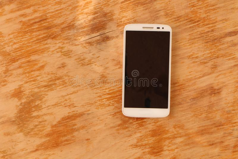 Close up - a white smartphone and a black smartphone on a wooden background royalty free stock images