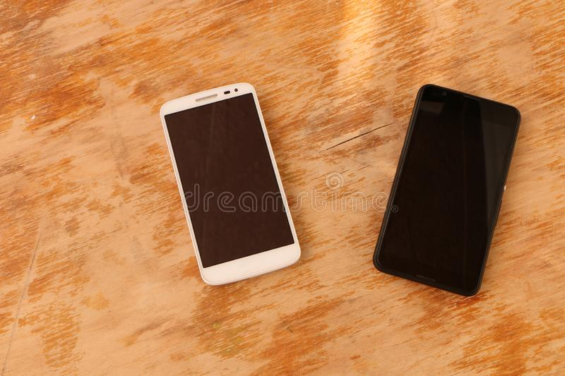 Close up - a white smartphone and a black smartphone on a wooden background royalty free stock photo