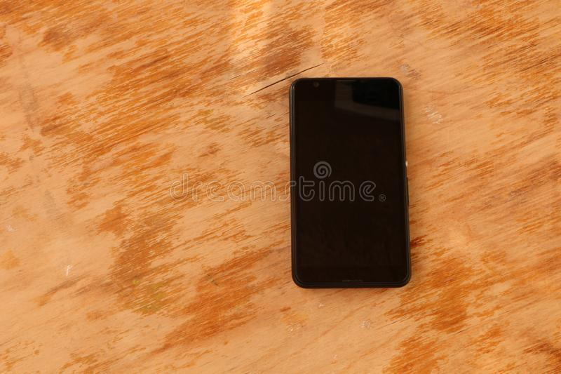 Close up - a white smartphone and a black smartphone on a wooden background royalty free stock photography