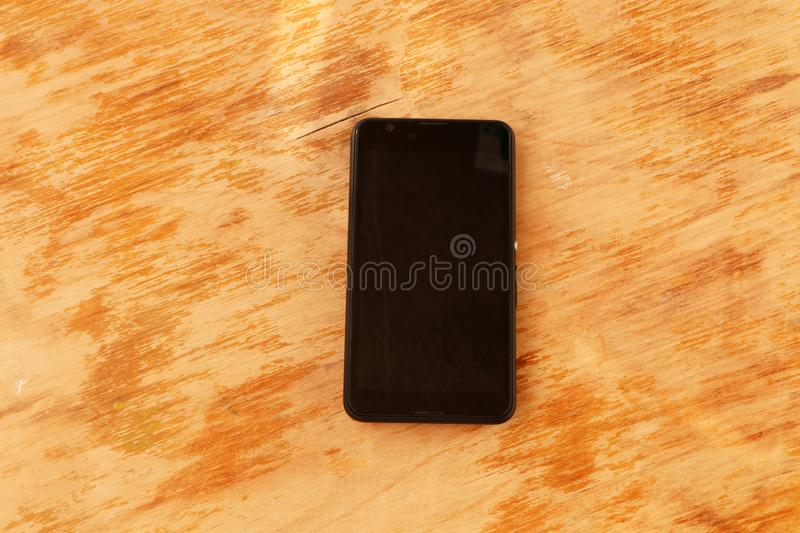 Close up - a white smartphone and a black smartphone on a wooden background royalty free stock image