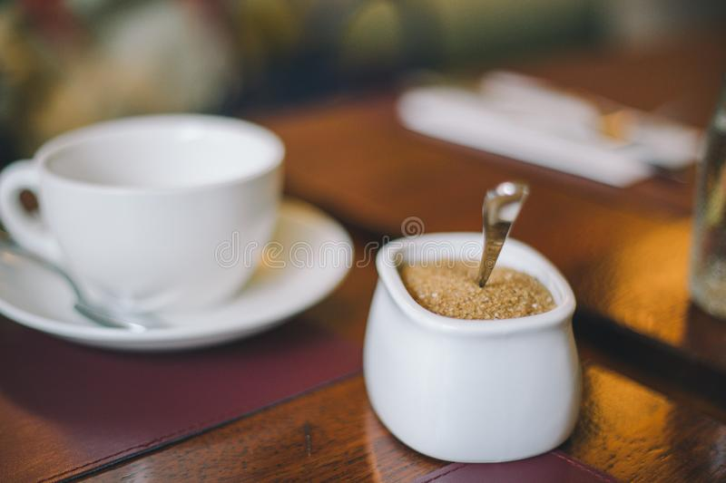 Close-up white sugar bowl with brown sugar on a white cup with a saucer on the table royalty free stock image