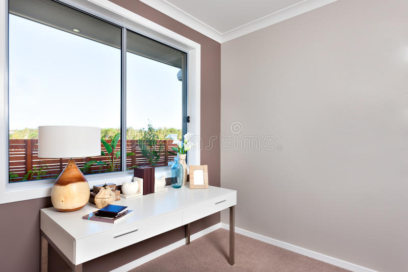 Close up of a white table with books and ornamental items isolated near the glass window in a modern room royalty free stock image