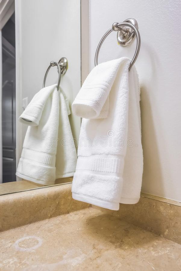 Close up of a white towel hanging on a metal ring mounted on the bathroom wall royalty free stock photography