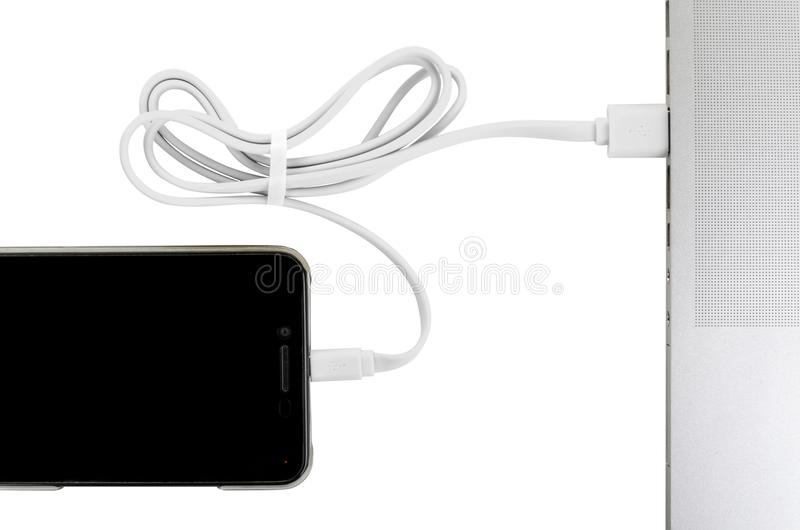 Close-up white usb cable connect phone and laptop computer new technology concept. Horizontal frame stock photo