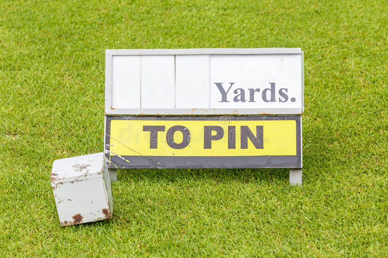 Close-up white wooden tee off area or tee box with length inform. Ation sign in background royalty free stock image