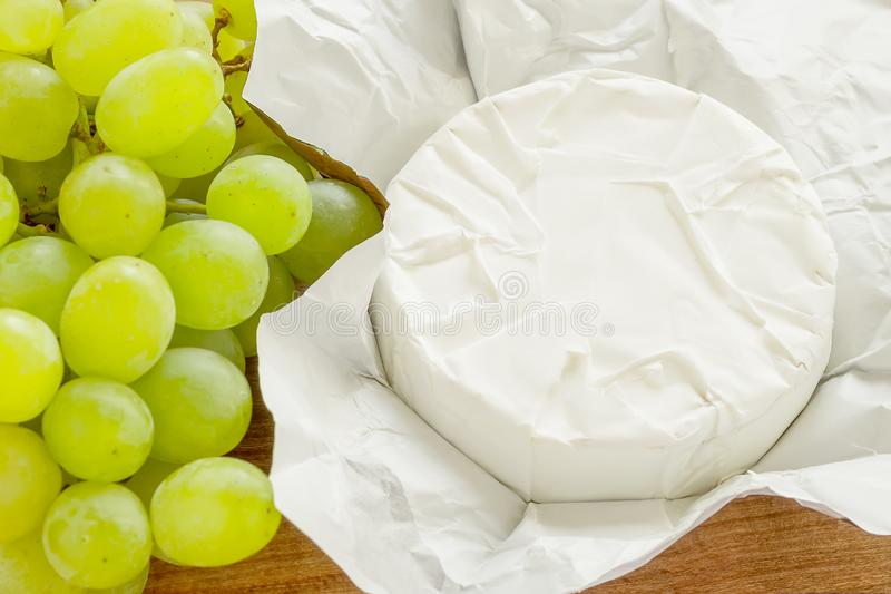 Close-up of whole head of camembert in just open paper package and sweet green grapes on a brown wooden cutting board. Soft cheese covered with edible white stock images